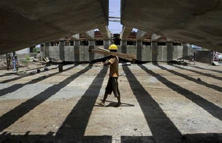 A worker carries pieces of wood at the construction site of a flyover bridge in Chennai July 18, 2011. REUTERS/Babu/Files