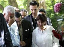 <p>Father Mitch Winehouse (L-R), brother Alex, former boyfriend Reg Traviss and mother Janis look at look at memorabilia left by fans of Amy Winehouse outside her house in London July 25, 2011. REUTERS/Luke MacGregor</p>