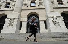 <p>A woman walks past Milan Stock Exchange July 12, 2011. REUTERS/Paolo Bona</p>