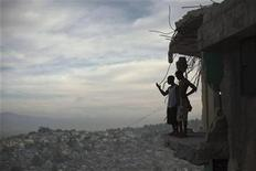 <p>Orich Florestal (L), 24 and Rosemond Altidon, 22, stand on the edge of their partially destroyed apartment of Port-au-Prince January 9, 2011. REUTERS/Allison Shelley</p>