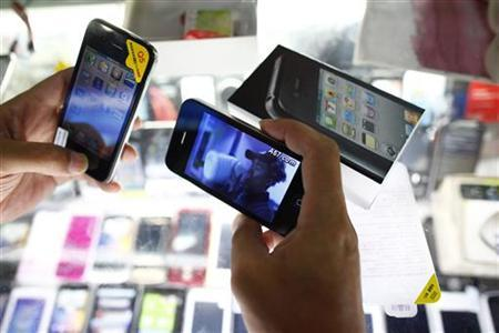 A person holds fake iPhones being sold at a mobile phone stall in Shanghai August 11, 2011. REUTERS/Aly Song