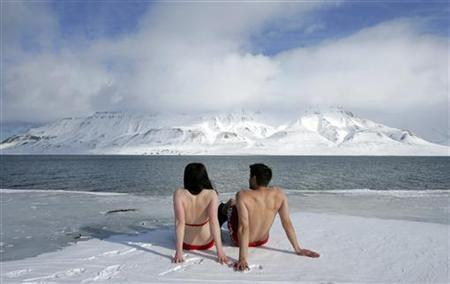 Climate activists Lesley Butler and Rob Bell (R) ''sunbathe'' on the edge of a frozen fjord in the Norwegian Arctic town of Longyearbyen April 25, 2007. REUTERS/Francois Lenoir