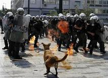 <p>Riot policemen try to avoid an exploding petrol bomb thrown by protesters during a demonstration in Athens' Syntagma (Constitution) square October 5, 2011. REUTERS/Yannis Behrakis</p>