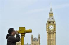 <p>A man looks through a telescope opposite Big Ben and the Houses of Parliament, in central London May 6, 2011. REUTERS/Toby Melville</p>