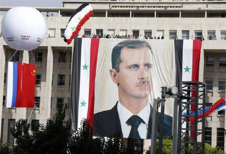 A Russian and a Chinese flag hang from a balloon during a rally of supporters of Syrian President Bashar al-Assad at al-Sabaa Bahrat square in Damascus October 12, 2011. REUTERS/ Khaled al-Hariri
