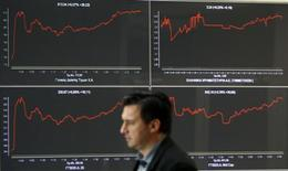 <p>A man walks past an index board at a hall of the Athens Stock Exchange, October 27, 2011. REUTERS/Yiorgos Karahalis</p>