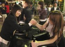 """<p>Mai Takahashi (R) and her friend arm wrestle during a """"Street Arm"""" event on a pedestrian street in the shopping district of Sendai, Miyagi prefecture October 8, 2011. REUTERS/Christopher Gallagher</p>"""