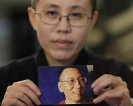 <p>Liu Xia, the wife of Chinese dissident Liu Xiaobo, holds a photo of Liu Xiaobo during an interview in Beijing October 3, 2010. REUTERS/Petar Kujundzic</p>