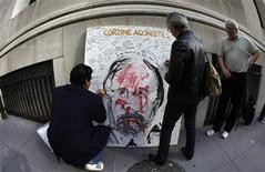 "<p>Artist Geoffrey Raymond (R), famous for his paintings of troubled Wall Street figures stands by his latest work ""Corzine Agonistes"" of former MF Global Chief and New Jersey Governor John Corzine as people write messages on the canvas across Broad Street from the New York Stock Exchange in New York, November 10, 2011. REUTERS/Mike Segar</p>"