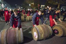 <p>Men roll barrels of Beaujolais Nouveau wine for the official launch of the 2011 vintage in the center of Lyon early November 17, 2011. REUTERS/Robert Pratta</p>