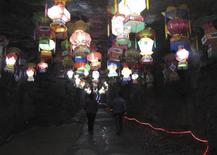 <p>Visitors walk past lanterns in the underground cave portion of the Underground Fluorescent park in Yishui November 4, 2011. REUTERS/Melanie Lee</p>