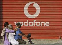 <p>Imagen de archivo de unas personas frente a una sucursal de la firma Vodafone en Jammu, India, nov 21 2011. Vodafone, el mayor operador mundial de telefonía móvil por ingresos, presentó el lunes planes para expandirse con nuevas sociedades de operación en Asia y Sudamérica. REUTERS/Mukesh Gupta</p>