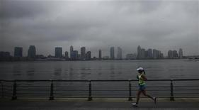 <p>A woman jogs before the arrival of Hurricane Irene at downtown Manhattan in New York August 27, 2011. REUTERS/Eduardo Munoz</p>