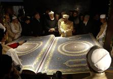 <p>Calligrapher Mohammad Sabir Khedri (centre right) gives information about the biggest Koran in the world to Afghan officials during its inauguration ceremony in the Hakim Nasir Khosrow Balkhi library in Kabul January 12, 2012. REUTERS/Mohammad Ismail</p>