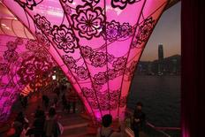 <p>A shopper takes a photo at a shopping mall decorated for the upcoming Chinese New Year, with office tower Two IFC in the background in Hong Kong January 19, 2012. REUTERS/Bobby Yip</p>