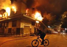 <p>A cyclist rides past a burning building during violent protests in central Athens, February 12, 2012. REUTERS/Yannis Behrakis</p>