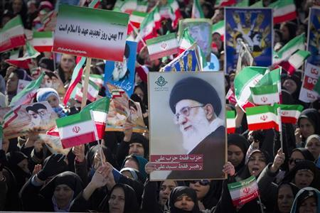 Demonstrators wave the Iranian flag and hold a picture of Supreme Leader Ayatollah Ali Khamenei during a ceremony to mark the 33rd anniversary of the Islamic Revolution, in Tehran's Azadi square February 11, 2012. REUTERS/Caren Firouz