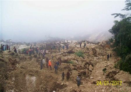 People walk over a landslide in Nogoli in this January 24, 2012 file handout photo. REUTERS/Handout/Files