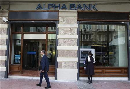 A woman makes a transaction at an ATM machine outside an Alpha Bank branch in Athens March 9, 2012. REUTERS/John Kolesidis