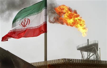 Gas flares from an oil production platform, as an Iranian flag is seen in the foreground, at the Soroush oil fields in the Persian Gulf, some 1,250 km (776 miles) south of the capital Tehran in this July 25, 2005 file photo. REUTERS/Raheb Homavandi