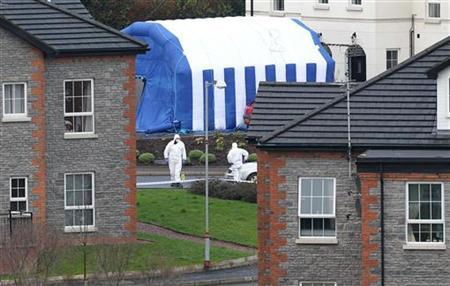 Police Service of Northern Ireland forenics officers attend the scene of a bomb attack that killed 25 year old police constable Ronan Kerr outside his home in Omagh, Northern Ireland April 3, 2011. REUTERS/stringer