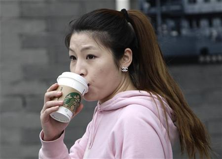 A woman drinks a cup of Starbucks coffee as she leaves a store at Qianmen Commercial Street in central Beijing, April 19, 2012. REUTERS/Jason Lee