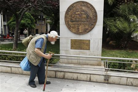A man makes his way past a replica of a one drachma coin outside the Athens Town Hall May 21, 2012. REUTERS/Yorgos Karahalis