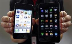 <p>Imagen de archivo de un empleado de la firma de telecomunicaciones KT con un iPhone 4 de Apple (izquierda en la imagen) y con un Galaxy S II de Samsung en la casa matriz de la firma en Seúl, ago 25 2011. La selección del jurado para la disputa de patentes entre Apple y Samsung Electronics comenzó el lunes en Estados Unidos, en la culminación de un año de batalla prejudicial que tiene millones de dólares en juego. REUTERS/Jo Yong-Hak</p>