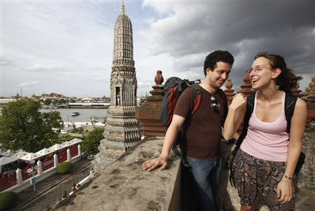 Tourists share a laugh during a visit the Temple of the Dawn in Bangkok August 2, 2012. REUTERS/Chaiwat Subprasom