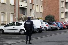 <p>Policier près de l'appartement toulousain de Mohamed Merah où les forces de l'ordre ont lancé l'assaut en mars. Un homme et son épouse ont été arrêtés mardi matin dans la région de Toulouse dans l'enquête sur les crimes de Mohamed Merah, qui a abattu sept personnes en mars à Toulouse et Montauban. /Photo prise le 23 mars 2012/REUTERS/Jean-Paul Pélissier</p>
