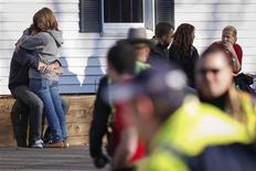 <p>Des proches de victimes de la tuerie de l'école élémentaire de Newtown, dans le Connecticut. Un homme lourdement armé a ouvert le feu vendredi matin dans l'école, tuant au moins 26 personnes, dont 20 enfants. /Photo prise le 14 décembre 2012/REUTERS/Adrees Latif</p>