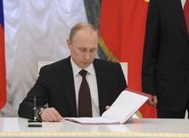 Les investisseurs commencent à craindre les effets de l'alourdissement des sanctions plus sévères qu'anticipé décidées par Washington à l'encontre du premier cercle des proches de Vladimir Poutine dans la foulée de l'annexion de la Crimée par la Russie. /Photo prise le 21 mars 2014/REUTERS/Mikhail Klimentyev/RIA Novosti/Kremlin