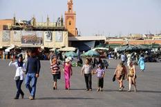Tourists walk around the Argana restaurant (background) at Marrakesh?s famous Jemma el-Fnaa square, June 22, 2012.    REUTERS/Abderrahmane Mokhtari