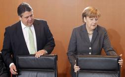 La chancelière Angela Merkel et son ministre de l'Économie, et de l'Énergie Sigmar Gabriel. Le gouvernement allemand a adopté mardi une réforme de la loi sur les énergies renouvelables. Le texte, auquel Sigmar Gabriel tenait, freinera la hausse des coûts de l'électricité et aussi ralentira le développement de l'énergie verte, qui représente 25% de la production nationale d'électricité. /Photo prise le 8 avirl 2014/ REUTERS/Fabrizio Bensch