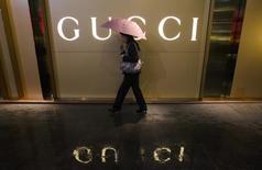 Женщина с зонтом проходит мимо магазина Gucci в Гуанчжоу 25 февраля 2014 года. Итальянский модный бренд Gucci, принадлежащий французской Kering, получит прямой контроль над своими московскими магазинами, работающими по франшизе, и откроет две новых точки  в столице РФ, сообщила компания в понедельник. REUTERS/Alex Lee