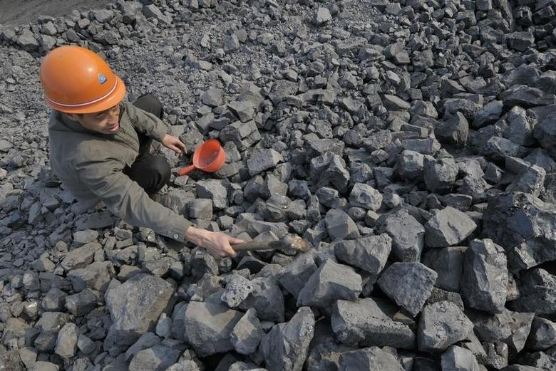 An Employee from a steel plant examines the quality of the iron ore at a railway freight station in Yingtan, Jiangxi province, November 11, 2010. REUTERS/Stringer/Files