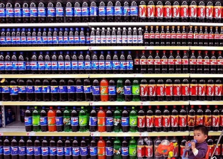 A boy sitting in a toy tricycle is pushed past shelves of bottled beverages at a supermarket in Nanjing, east China's Jiangsu province April 10, 2006. REUTERS/Stringer