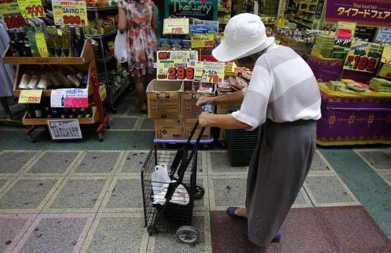 A woman pushing a cart looks at items at a local shopping street in Tokyo August 12, 2013. REUTERS/Yuya Shino