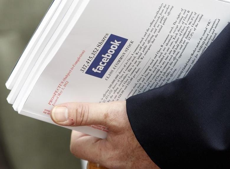 An investor holds prospectus explaining the Facebook stock after attending a show for Facebook Inc's initial public offering at the Four Season's Hotel in Boston, Massachusetts May 8, 2012. REUTERS/Jessica Rinaldi/Files