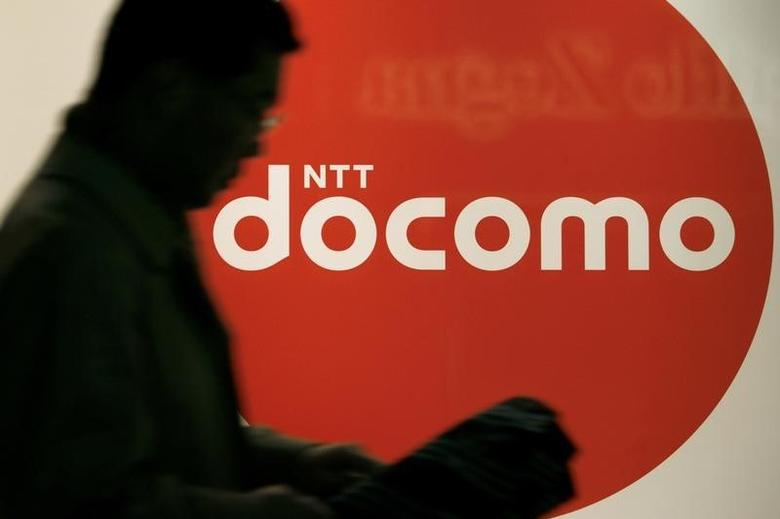 A man walks past the logo of Japan's biggest mobile phone operator NTT docomo, Inc. at its shop in Tokyo November 28, 2008. REUTERS/Stringer/fILES
