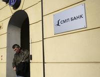 Мужчина у отделения СМП-банка в Москве 24 марта 2014 года. Минфин США ввел санкции против российских СМП-банка и Инвесткапиталбанка, принадлежащих Аркадию и Борису Ротенбергам, сообщило американское ведомство в понедельник. REUTERS/Maxim Zmeyev