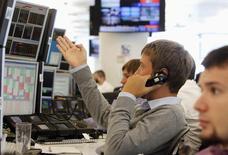 Трейдеры в торговом зале инвестбанка Ренессанс Капитал в Москве 9 августа 2011 года. Российский фондовый рынок сохраняет во вторник заряд бодрости, поводом для которой накануне стали достаточно мягкие, по мнению участников торгов, санкции США в отношении РФ, которые не затронули крупные публичные компании. REUTERS/Denis Sinyakov