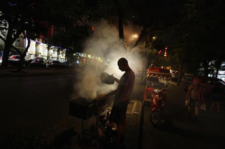 A man fans a grill while cooking kebabs at a roadside stall, in central Beijing August 10, 2012. REUTERS/Jason Lee