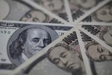 Купюры валюты иена и доллар США в Токио 28 февраля 2013 года. Курс иены к доллару растет, после того как Банк Японии в соответствии с прогнозом воздержался от дополнительных стимулов. REUTERS/Shohei Miyano