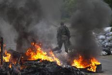 Пророссийский сепаратист охраняет блокпост около украинского города Славянска, 2 мая 2014 года Киев стянул войска к контролируемому пророссийскими сепаратистами Славянску, пригнав бронетранспортеры с десантниками и вертолеты, уже есть погибший и раненые. REUTERS/Baz Ratner (UKRAINE - Tags: POLITICS CIVIL UNREST) - RTR3NHQL