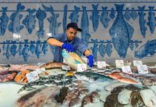 Продавец раскладывает рыбу в магазине  Frische Paradies в Берлине 13 февраля 2014 года. Риск дефляции в еврозоне очень низкий, но рост цен в текущем и следующем годах будет более медленным, чем ожидалось, отчасти из-за сильного евро и слабого восстановления экономики, сообщила в понедельник Еврокомиссия. REUTERS/Thomas Peter