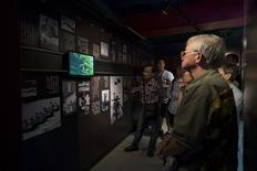 Visitors watch a video showing Chinese army soldiers entering Tiananmen Square at a museum dedicated to the 1989 pro-democracy protests and crackdown, in Tsim Sha Tsui April 27, 2014. REUTERS/Tyrone Siu