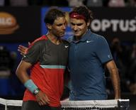 Rafael Nadal (L) of Spain and Roger Federer of Switzerland hug at the net, after Nadal won  their men's singles semi-final match at the Australian Open 2014 tennis tournament in Melbourne January 24, 2014. REUTERS/Bobby Yip