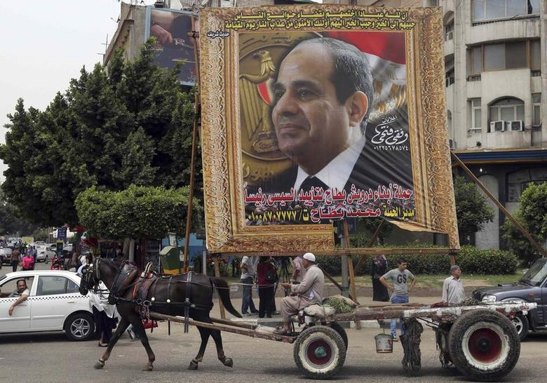An Egyptian man on horse cart rides past a huge banner for Egypt's former army chief Field Marshal Abdel Fattah al-Sisi in downtown Cairo, May 6, 2014. REUTERS/Mohamed Abd El Ghany