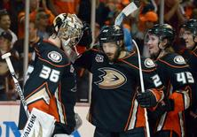 May 12, 2014; Anaheim, CA, USA; Anaheim Ducks goalie John Gibson (36) is congratulated by center Matheiu Perreault (22) and defenseman Sami Vatanen (45) after game five of the second round of the 2014 Stanley Cup Playoffs against the Los Angeles Kings at Honda Center. The Ducks defeated the Kings 4-3 to take a 3-2 series lead. Mandatory Credit: Kirby Lee-USA TODAY Sports